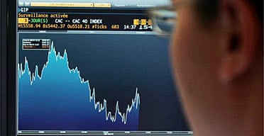 A broker works as his control screen shows a graph of activity on the stock exchange in Paris