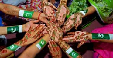Students show their hands painted with henna and national flags