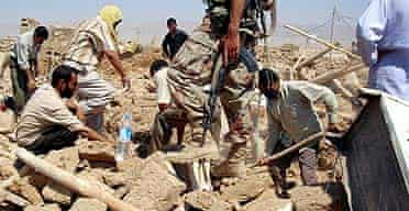 Men dig through rubble to search for survivors and dead on after  coordinated suicide attacks in the town late of Qahataniya, 75 miles west of Mosul.