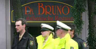 German investigators pass in front of the Da Bruno Italian restaurant in the town of Duisburg, where six men were shot dead in an apparent Mafia vendetta