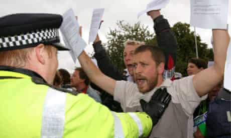 Climate change protestors are held back by police officers