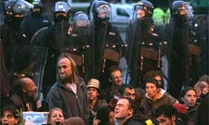 Police in riot gear stand behind protesters blocking the BAA entrance. Photograph: Lefteris Pitarakis/AP