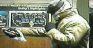 CCTV image of Nicki Jex holding up a bookmakers shop using a concealed sex toy