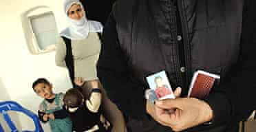 The father of a 14-year-old girl who committed suicide holds photos of her at the family's near Batman in south-east Turkey
