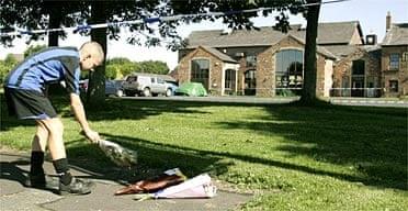 A boy lays flowers outside the Fir Tree pub in Croxteth, Liverpool where 11-year-old Rhys Jones was shot dead