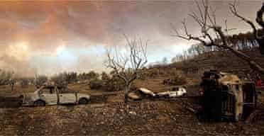 Burned cars sit in a field near Artemida, one of the villages caught in the fires which have spread through the Peloponnese forests