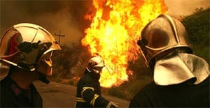 Firefighters try to contain the blaze outside Andritsena village in the Pelloponese
