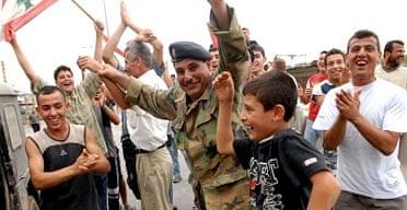 A Lebanese soldier and local residents celebrate the end of fighting in the Nahr el-Bared refugee camp