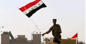 An Iraqi soldier waves the national flag outside Basra Palace. Photograph: Nabil al-Jurani/AP
