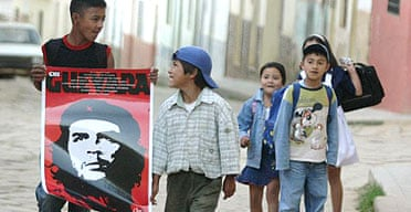 A boy in Vallegrande, Bolivia, holds a poster of Che Guevara