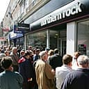 Customers of Northern Rock queue outside the Kingston branch of the company on Castle Street, in order to take their money out of their accounts