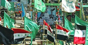 Flags fly at a cemetery in Najaf, the day after more than 200 people were killed in a series of coordinated attacks in the city