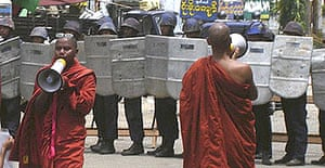 Protesting monks use loudhailers to address onlookers in front of riot as Burmese riot police close in
