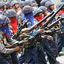 Armed Burmese security forces march down the streets of Rangoon to quell protests