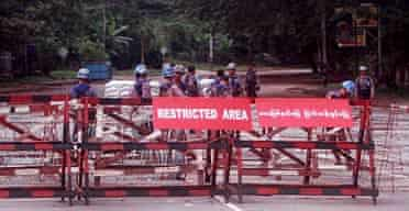Myanmarese policemen at the checkpoint leading to the house of opposition leader Aung Sang Suu Kyi in Yangon, Burma.