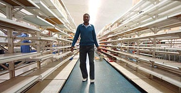 A Zimbabwean shopper walks past empty shelves at a supermarket in Harare