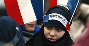 """A Muslim girl has two French flags and a headband which reads """"fraternity"""" on her headscarf during a protest defending religious headgear in 2004."""