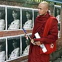 A Buddhist monk looks at posters of Burmese democracy leader Aung San Suu Kyi in New Delhi, India.