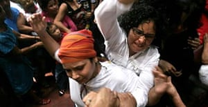 Members of a Nicaraguan feminist group fight with Catholic faithful during a mass inside a cathedral in Managua