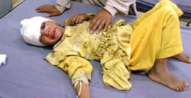 A paramedic treats a girl injured in an air strike in Waziristan