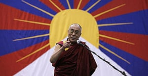 Framed by the Tibetan flag, the Dalai Lama speaks to members of the Tibetan Community in New York.