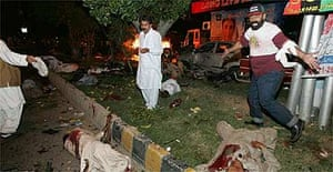 Bodies lie on a road in Karachi, Pakistan after a bomb attack targeting former prime minister Benazir Bhutto