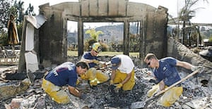 La Mesa firefighters dig through the wreckage of a fellow firefighter's home in San Diego