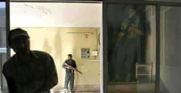 Afghan police stand guard during a raid at Olympus private security in Kabul