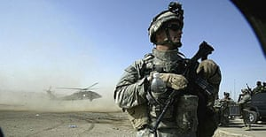 A US soldier stands guard as a Blackhawk helicopter lands in Kerbala, Iraq.