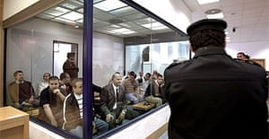 A police officer stands in front of a glass cage holding the Madrid train bomb suspects at their trial at Spain's national court