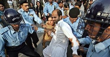 Pakistani policemen arrest human rights activists.