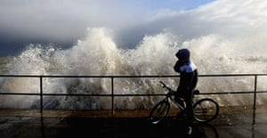 A cyclist is caught out by a huge wave in Great Yarmouth