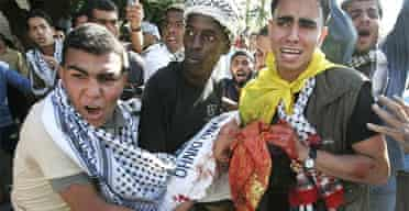 Palestinians carry a wounded Fatah supporter in Gaza City