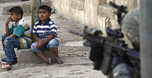 Two children sit in front of a US soldier from 2nd Stryker Cavalry Regiment on patrol in Baghdad