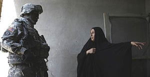 A US soldier from the 2nd Stryker Cavalry Regiment talks to a local resident during a patrol in Baghdad