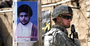 A US soldier on patrol in Baghdad stands next to a poster of the radical Shia cleric Moqtada al-Sadr