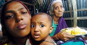 Three generations of a Bangladesh family sit inside a makeshift shelter in Chailtatoli village on the south coast