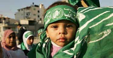 A Palestinian child wears a Hamas flag.