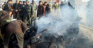 Afghan police inspect the wreckage of a smoking suicide attacker's vehicle following a blast in which eight civillians were wounded in Kabul, 04 December 2007.