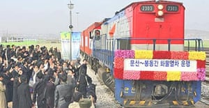 North Koreans at Panmun station in Kaesong greet the first train since 1950 to cross the border