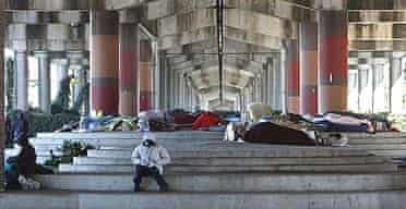 People gather underneath Interstate 10 where over 100 homeless locals sleep each night in New Orleans.