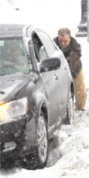 A man pushes a stranded car out of snow in Minneapolis, Minnesota
