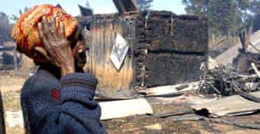 A woman outside the church in Eldoret, where up to 50 people, many of them children, were burned alive after they came under siege