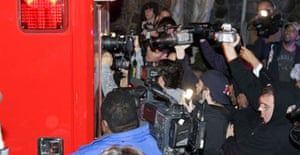 Photographers try to get a shot through the back window of a Los Angeles City Fire Department ambulance, believed to carrying entertainer Britney Spears, as it leaves her residenceJanuary 3 2008, in Los Angeles.