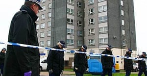 Police officers search the area in front of Verona House in Erith, where a teenage boy was stabbed to death
