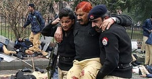 Pakistani police help an injured colleague at the suicide attack site in Lahore