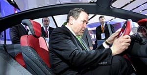 Presidential hopeful Mike Huckabee sits in the driver's seat of a Ford Verve Concept at the Detroit car show