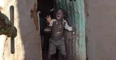 A Kenyan boy screams as he sees a Kenyan policeman with a baton approach the door of his home in the Kibera slum of Nairobi