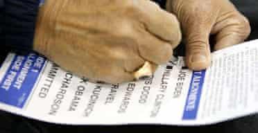 Jose Calimag marks his Democrat presidential preference card in Las Vegas. Photograph: Ronda Churchill/AP