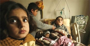 A Palestinian boy waits to pump air into his bedbound brother's lungs in case his respirator cuts out